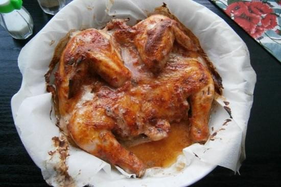 Каждая хозяйка обязана хоть раз в жизни сделать это легендарное блюдо грузинской кухни! Тот самый цыпленок табака! Если вы еще не пробовали приготовить его на своей кухне, то пора это исправить. Наш рецепт диетический - цыпленок в духовке, а также запеченные корнишоны. Присоединяйтесь!  Деликатес по мотивам грузинской кухни - цыпленок табака Если на вашем столе появится восхитительно вкусный цыпленок табака, приготовленный в духовке, гости и домочадцы будут в полном восторге. Это блюдо станет гвоздем праздничного стола! В традиционной версии его жарят под гнетом в толстой сковороде. В нашем варианте он будет менее калорийным, но у него сохранится поджаристая и хрустящая корочка, характерный цвет и сочность. Ингредиенты: •цыпленок - 800 г; •сметана - 2 стол. ложки; •аджика - 3 стол. ложки; •перец чили; •молотый перец - 0,5 чайн. ложки; •петрушка сушеная - 2 стол. ложки; •соль; •чеснок - 2 зубка; •вода - 30 мл; •приправы (тмин, хмели-сунели, шафран); •лимонный сок - 1/2 чайн. ложки. Фото 1 Приготовление: 1.Цыпленка вымойте под прохладной проточной водой. Обсушите бумажным полотенцем (лишняя влага вам ни к чему). 2.Внимательно изучите тушку. Если на ней остались перышки, удалите их. 3.Острым ножом сделайте разрез на внутренней стороне грудки. Фото 2 4.Расплющите цыпленка, поместив его разделочную доску. Фото 3 5.Отбейте его с обеих сторон кулинарным молоточком.  Фото 4 6.Если не хотите, чтобы по всей кухне летели брызги, прикройте тушку пищевой пленкой! И не переусердствуйте, перед вами не стоит задача поломать кости! Фото 5 7.Хорошо помните руками суставы и позвонки птицы, как бы выворачивая наизнанку. 8.Тушку посолите с каждой из сторон. Фото 6 9.Выложите в глубокую миску 3 ложки аджики. 10.Добавьте к ней специи, перец (жгучий и молотый). Положите сметану. Фото 7 11.Все ингредиенты соуса хорошенько перемешайте. Фото 8 12.Обмажьте подготовленную тушку острым соусом. Оставьте птицу в пряном маринаде на час, помесив ее на полку холодильника, или пусть постоит 15 минут н